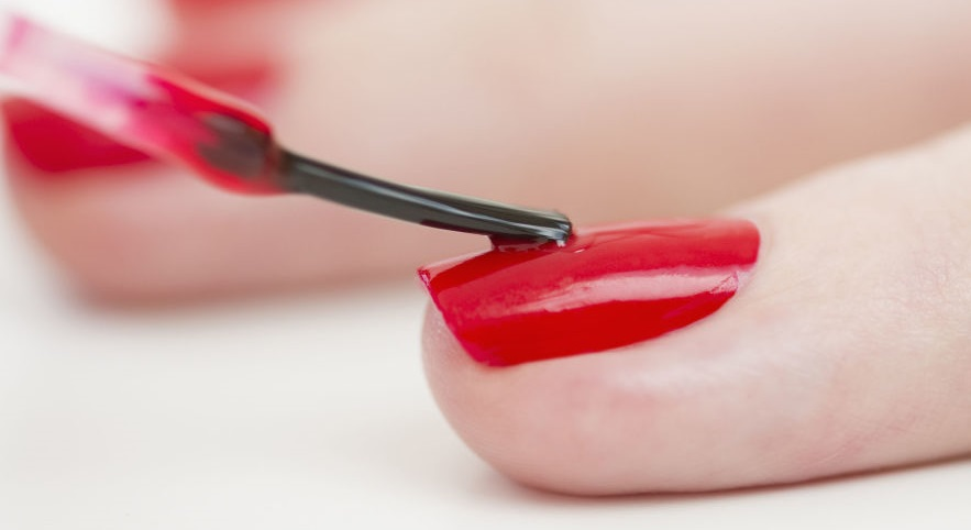 applying coats of nail paint on nails of hands
