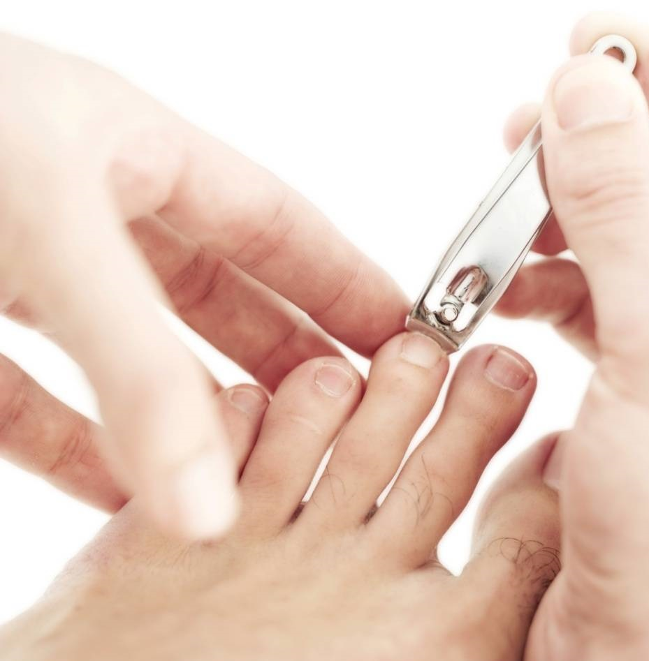 trimming nails with a nail clipper