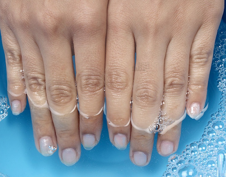 washing nails in a bowl of water