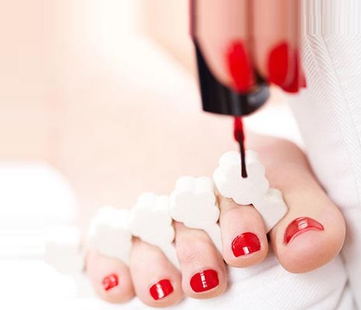 applying nail paint on feet nails